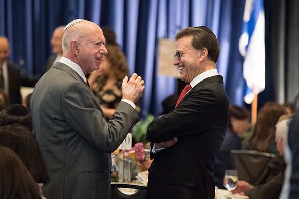 27th Awards Luncheon Dr. Bruce Powell (left), head of school at Los Angeles' de Toledo High School, greets Lowell Milken, chairman and co-founder of the Milken Family Foundation.