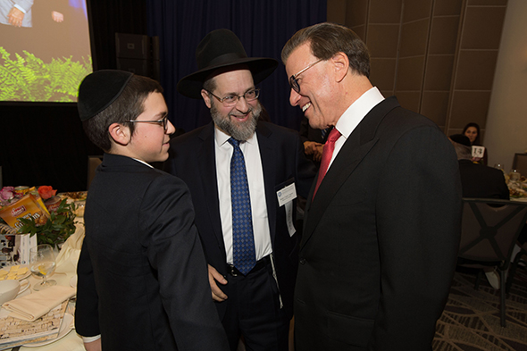 27th Awards Luncheon Lowell Milken (right), chairman and co-founder of the Milken Family Foundation, talks with 2016 Jewish Educator Award recipient Rabbi Chaim Trainer and his son.