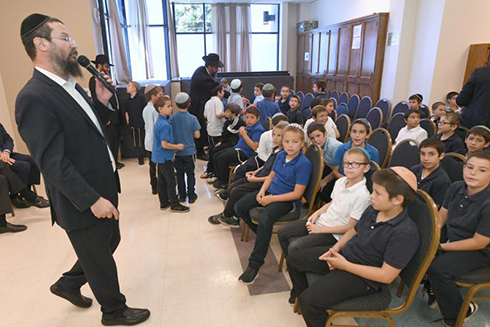Yehudis Blauner Notification At Cheder Menachem, Rabbi Menachem Mendel Greenbaum, the school's principal and a 2014 Jewish Educator Award recipient, settles students before the assembly.