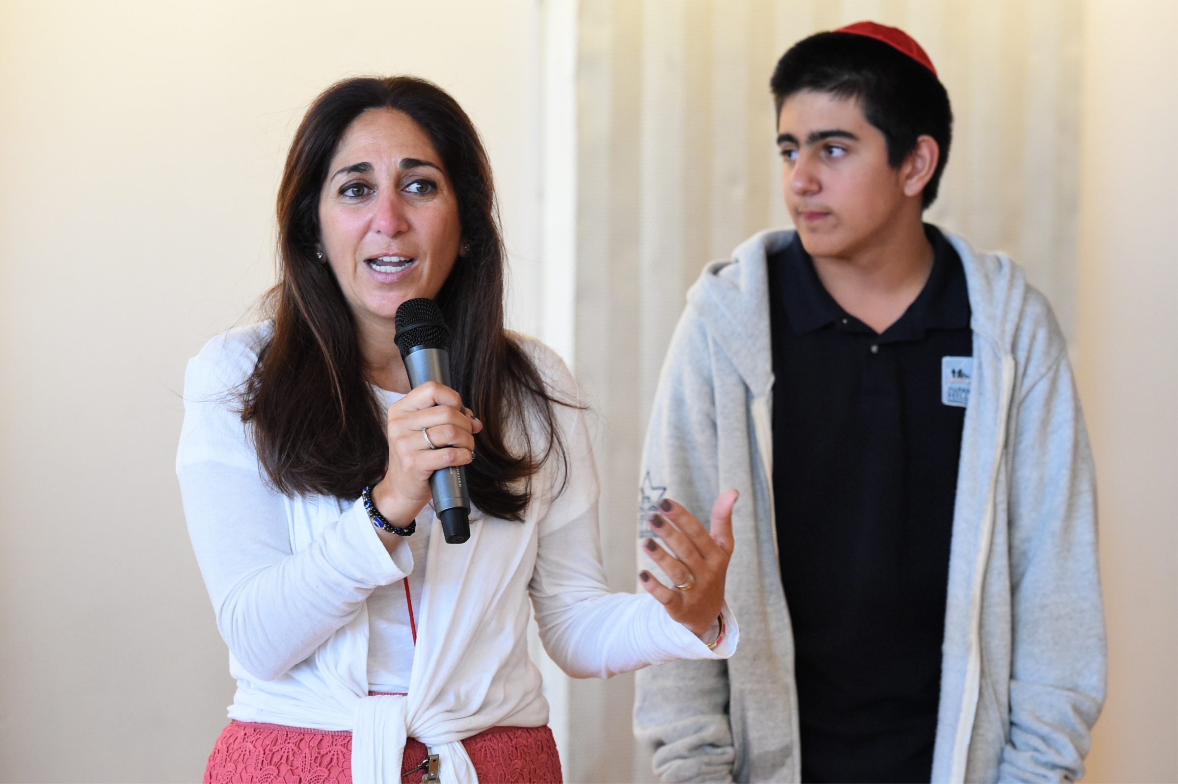 Florette Benhamou Notification Florette Benhamou shares some thoughts with the audience as her son Dylan, a Harkham Hillel seventh-grader, looks on.